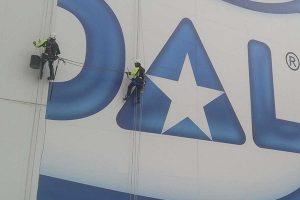 trabajos verticales para instalar un logotipo de grandes dimensiones