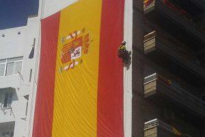 trabajo vertical para instalar una bandera el día de la hispanidad